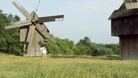 The beautiful ukrainian girl running on the background of an old mills. The beautiful ukrainian girl running on village. She holding in her hands bouquet of stock footage