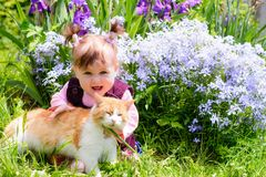 A beautiful Ukrainian little girl playing on a lawn with an ore cat royalty free stock images