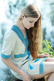 Beautiful ukrainian woman. Outdoor in national clothes sitting near the lake Royalty Free Stock Photography