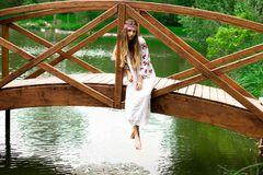 Steep slender Ukrainian woman resting sitting on a wooden decorative bridge over the water on a hot sunny day royalty free stock image