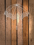 Beautiful umbrella over wood. Beautiful umbrella with drops over wood background Royalty Free Stock Photos