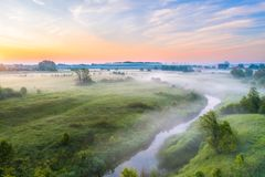Beautiful underground fog over a small river among grassy meadows in rural areas, early in the morning at dawn.  royalty free stock image