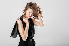 Woman in black with shopping bag. Beautiful unhappy curly woman in black elegant overall with shopping bag. sale Royalty Free Stock Photo