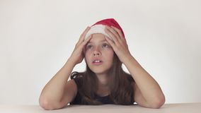 Beautiful unhappy girl teenager in a Santa Claus hat emotionally expresses despair and begins to cry on white background stock video