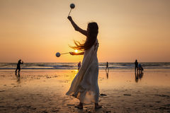 Beautiful unidentified woman dancing at sunset Stock Photos
