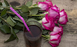 Beautiful union of roses and glass of juice Royalty Free Stock Images