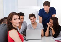 Beautiful university student sitting with classmates. Portrait of beautiful university student sitting with classmates using laptop in classroom Stock Photo