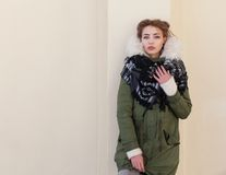 Beautiful unusual girl in a green jacket on background light wall Stock Photos
