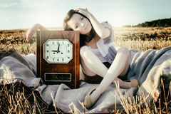 Beautiful unusual girl illustrates conceptual idea with watch Stock Photos