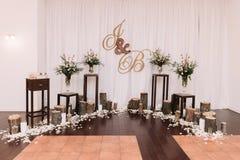 Beautiful unusual wedding decor. Stubs, rose petals, bouquets and monogram Stock Photos