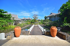 Beautiful upscale resort hotel with small wooden bridge entrance connecting to the villas with two big pots Stock Photography