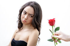 Beautiful upset girl receives one red rose. She is looking over her shoulder and pouts. Royalty Free Stock Photos