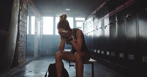 Beautiful upset sporty blonde woman sitting alone in dark gym locker room, wiping face tired after bad day slow motion. Attractive female athlete fighting a stock video footage
