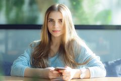 Beautiful upset young woman laying on a couch at home, using mobile phone stock image