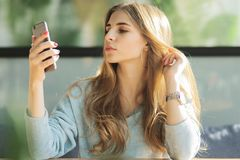 Beautiful upset young woman laying on a couch at home, using mobile phone royalty free stock images