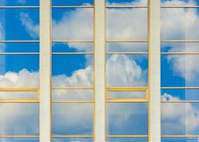 Beautiful urban architecture background. Window reflection of a clouds on a blue sky royalty free stock photo