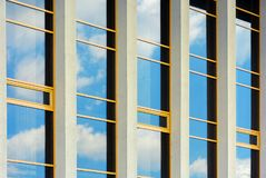 Beautiful urban architecture background. Window reflection of a clouds on a blue sky. perspective side view with four columns royalty free stock photo