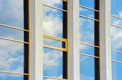 Beautiful urban architecture background. Window reflection of a clouds on a blue sky. perspective side view with three columns stock photography