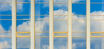 Beautiful urban architecture panoramic background. Window reflection of a clouds on a blue sky stock photos