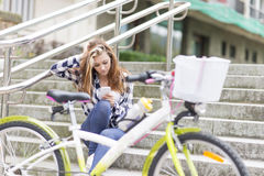 Beautiful urban girl with bicycle using  phone, adolescence life Stock Images