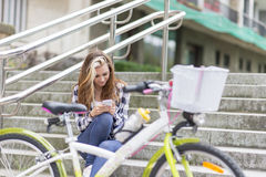 Beautiful urban girl with bicycle using  phone, adolescence life Royalty Free Stock Photo