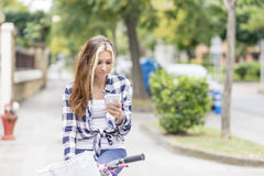 Beautiful urban girl with bicycle using  phone, adolescence life Royalty Free Stock Photography