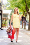 Beautiful urban girl standing on the street after shopping Stock Photos