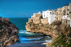 Beautiful urban landscape of Polignano a Mare overlooking the se. A. Blue sky and blue sea. The waves of the sea near the shore. The white stone walls of the Stock Photo