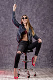 Beautiful urban trendy girl in black leather jacket and jeans posing on a high chair Royalty Free Stock Photos