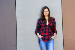 Beautiful urban woman, girl in jeans over bulding wall in three Stock Images
