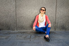Beautiful urban woman, girl siting by the wall in city. Royalty Free Stock Image