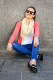 Beautiful urban woman, girl siting by the wall in city Stock Image