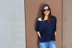 Beautiful urban woman, girl standing by the wall in city wering. Jeans Stock Images