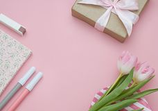 Feminine flat lay  frame with flowers and gift on the pink background. Copy space. Beautiful Valentines day background with flowers and gift. Flat lay. Top view Stock Photography