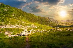 Beautiful valley of Fagaras mountains. Small brook flow among the rocks. grassy slopes with huge boulders Stock Images