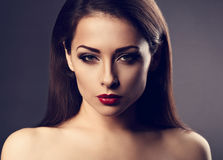 Beautiful vamp makeup sexy woman with hot red lipstick and long. Eye lashes looking expression on grey background in dramatic light. Closeup toned portrait Royalty Free Stock Photo