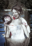 Beautiful vampire woman dressed white bloody shirt and her victi Stock Images