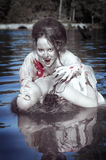 Beautiful vampire woman dressed white bloody shirt and her victi. Beautiful vampire women dressed white bloody shirt and her victim standing in the river Royalty Free Stock Photography