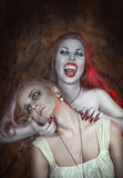 Beautiful vampire woman and her victim Stock Photos