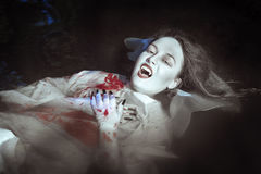 Beautiful vampire woman lying in the river Royalty Free Stock Image