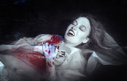 Beautiful vampire woman lying in the river Royalty Free Stock Images