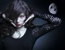 Beautiful vampire woman. Portrait of a beautiful female vampire background moon at night Stock Photography