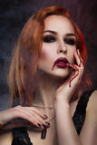 Beautiful vampire young woman. With hand and mouth covered in blood. Beauty shot. Bright makeup Stock Photography