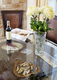 Beautiful vase with flowers and bottle of vine on glass diner ta Royalty Free Stock Photos