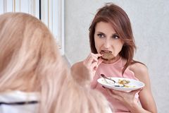 Beautiful vegetarian eating salad at home and listens to another woman.  Stock Image