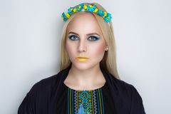Woman in traditional Ukrainian embroidery. Beautiful very bright blond woman in traditional Ukrainian embroidery. National colors yellow and blue fancywork cross royalty free stock photo