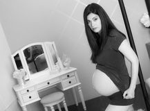 Beautiful Very Pregnant Woman Shows Belly in Bedroom Monochrome Royalty Free Stock Photo