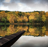 Beautiful vibrant Autumn woodland reflecions in calm lake waters Stock Photo