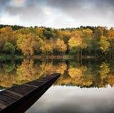 Beautiful vibrant Autumn woodland reflecions in calm lake waters Stock Photo