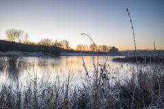 Beautiful vibrant English countryside lake image with frost and Royalty Free Stock Photo